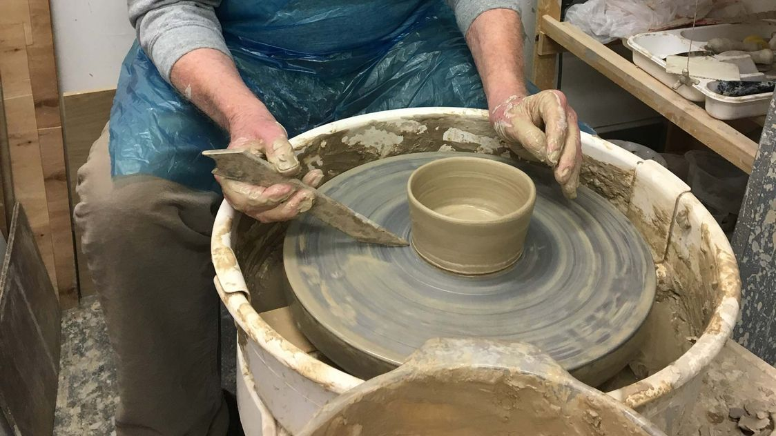 A older man working on some pottery