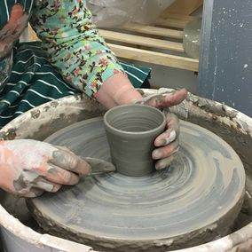 A woman working on a pottery wheel