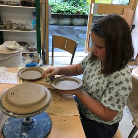 A young girl working on bespoke pottery